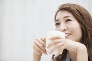 微笑みながら両手でカップを持つ女性の写真素材 [FYI02972441]