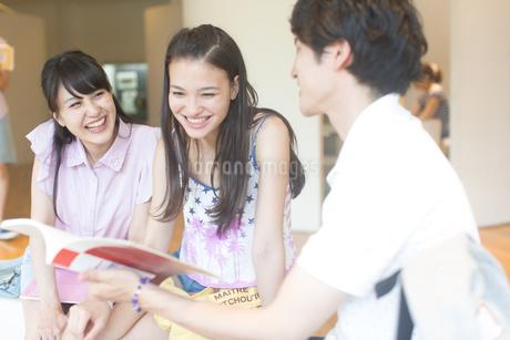 参考書を見ながら談笑する学生たちの写真素材 [FYI02972442]