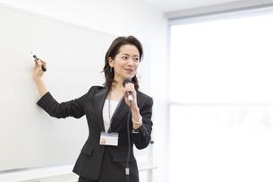 マイクを手に講義するビジネス女性の写真素材 [FYI02972449]