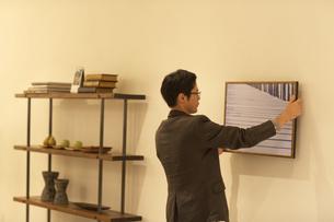 壁に写真を飾る男性の写真素材 [FYI02972450]