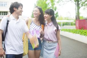 キャンパスで肩に手をかけて笑い合う学生たちの写真素材 [FYI02972452]