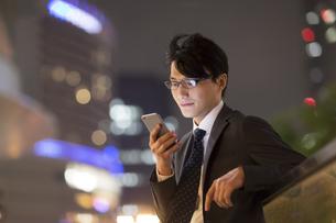 夜の街を背景にスマートフォンを見るビジネス男性の写真素材 [FYI02972455]