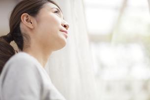 カーテンの傍で上を見上げる女性の写真素材 [FYI02972461]