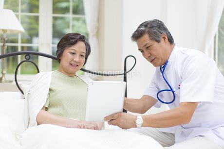 ベットのシニア女性にタブレットPCで説明する医者の写真素材 [FYI02972472]