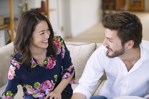 ソファーに座って微笑む男性と女性の写真素材 [FYI02972478]