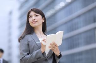 ビルを背景に立つビジネス女性の写真素材 [FYI02972481]