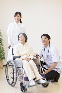 車椅子の患者に添う男性医師と女性看護師の写真素材 [FYI02972484]