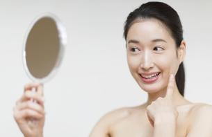 手鏡を見て微笑む女性の写真素材 [FYI02972485]