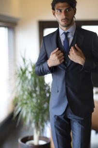 オフィスでスーツのジャケットを整えるビジネス男性の写真素材 [FYI02972488]