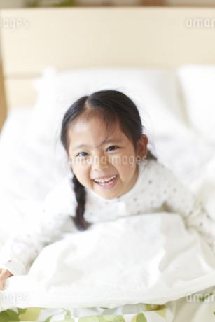 ベットの上で笑うパジャマ姿の女の子の写真素材 [FYI02972489]