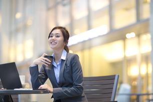 街中でカップを手に持ち微笑むビジネス女性の写真素材 [FYI02972495]