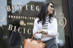 ウィンドウの前でサングラスをかけて微笑む女性の写真素材 [FYI02972497]