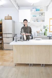 キッチンでコップを拭く女性の写真素材 [FYI02972505]