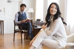 ソファーに座って微笑む女性と椅子に座って本を読む男性の写真素材 [FYI02972510]