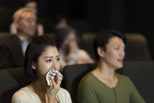 映画館で涙をこぼす女性の写真素材 [FYI02972516]