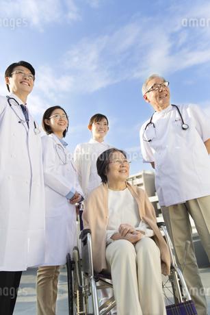 屋上で車椅子の患者に添う医師たちの写真素材 [FYI02972525]