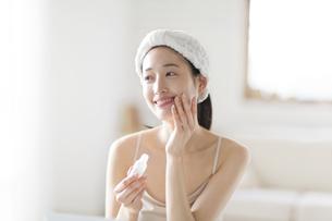 頬に手をあてスキンケアをする女性の写真素材 [FYI02972533]