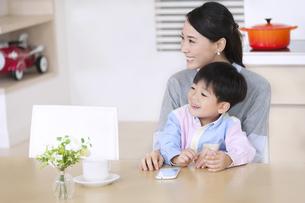 ダイニングテーブルで笑顔の母と男の子の写真素材 [FYI02972535]