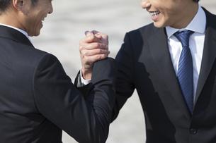 笑顔で手を組むビジネス男性2人の写真素材 [FYI02972541]