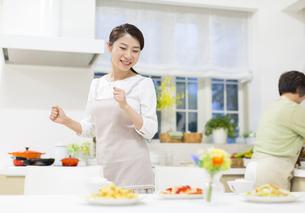 食卓の料理を見て喜ぶ若い奥さんの写真素材 [FYI02972549]
