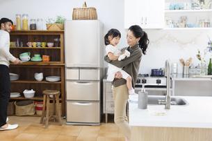 キッチンで食器の準備をする男性と子供をあやす女性の写真素材 [FYI02972554]