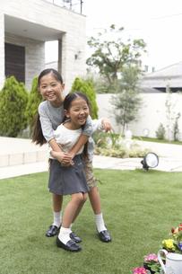 庭で身体を合わせて笑う姉妹のスナップの写真素材 [FYI02972556]