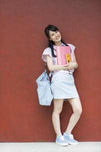赤い壁の前で微笑む女子学生のポートレートの写真素材 [FYI02972566]