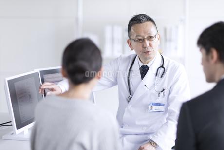 モニターを使って患者に説明をする男性医師の写真素材 [FYI02972568]
