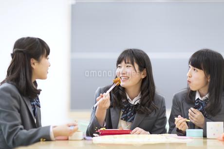 教室でお弁当を食べながら微笑む3人の女子高校生の写真素材 [FYI02972574]