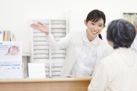 受付で患者に案内をする女性看護師の写真素材 [FYI02972577]