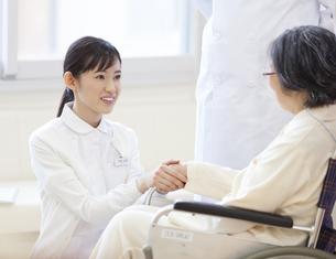 車椅子の患者の手に手を添える女性看護師の写真素材 [FYI02972583]