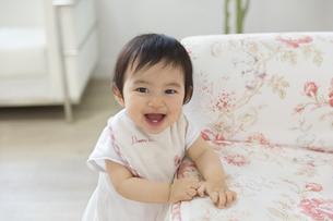 ソファーに寄りかかって微笑む赤ちゃんの写真素材 [FYI02972589]