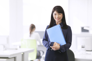 オフィスでファイルを持って微笑むビジネス女性の写真素材 [FYI02972592]
