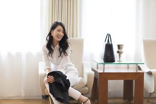 ソファーに座って笑う女性の写真素材 [FYI02972597]