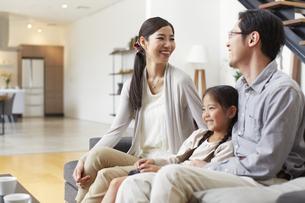 ソファーで会話する3人家族の写真素材 [FYI02972613]