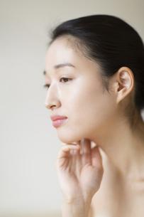 顎に片手を添える女性の写真素材 [FYI02972615]