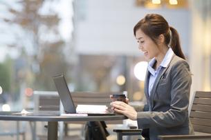 街中でノートPCを見て笑うビジネス女性の写真素材 [FYI02972617]