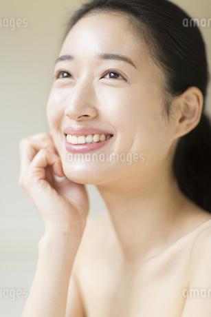 頬に片手を添えて上を見上げ微笑む女性の写真素材 [FYI02972622]