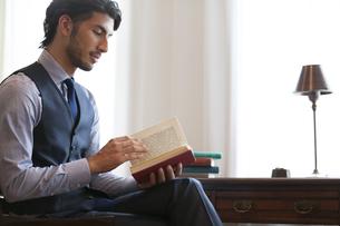 ソファーに座って本を読むビジネス男性の写真素材 [FYI02972626]