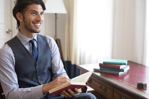 ソファーに座り本を持って微笑むビジネス男性の写真素材 [FYI02972631]