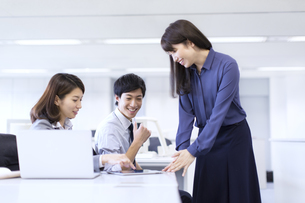 オフィスでタブレットPCを使って打ち合せをするビジネス男女の写真素材 [FYI02972632]