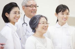 笑顔のシニア女性と医師たちの写真素材 [FYI02972634]