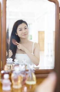 鏡台で髪をとかす女性の写真素材 [FYI02972636]