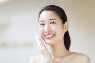 頬にコットンをあてスキンケアをする女性の写真素材 [FYI02972646]