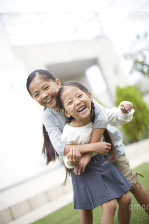 庭で身体を合わせて笑う姉妹のスナップの写真素材 [FYI02972649]
