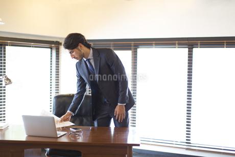 オフィスのデスクに資料を置くビジネス男性の写真素材 [FYI02972650]