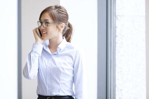 スマートフォンで通話するビジネス女性の写真素材 [FYI02972652]