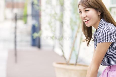 街中で遠くを眺め微笑む女性の写真素材 [FYI02972673]