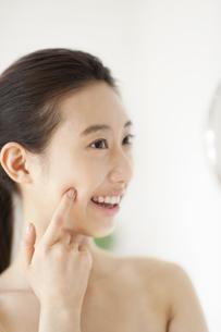 手鏡を見て微笑む女性の写真素材 [FYI02972674]