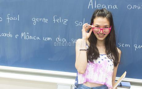 黒板の前で眼鏡を下して笑う女子学生のポートレートの写真素材 [FYI02972675]